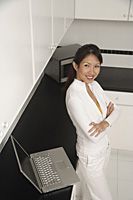Woman standing in kitchen with laptop and microwave, looking up at camera smiling - Asia Images Group