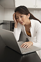 Woman in kitchen leaning on counter staring at laptop / computer, with head resting on hand - Asia Images Group