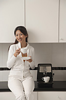 Woman sitting on counter in kitchen next to cappuccino machine, holding coffee, smiling, looking at camera. - Asia Images Group