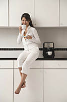 Woman sitting on counter in kitchen next to cappuccino machine, drinking coffee and looking at camera. - Asia Images Group