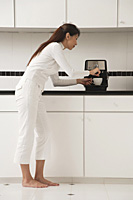 Woman in kitchen making coffee, cappuccino - Asia Images Group