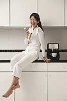Woman sitting on counter in kitchen next to a cappuccino / coffee machine, sending / receiving text message - Asia Images Group