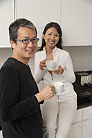 Woman sitting on counter in kitchen with man standing next to her, holding coffee cups, smiling and looking at camera. - Asia Images Group