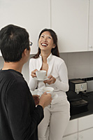 Woman sitting on counter in kitchen laughing with man facing her and his back towards camera.  both holding coffee cups. - Asia Images Group