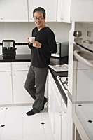 Man in kitchen, leaning on counter, holding coffee cup and smiling at camera - Asia Images Group