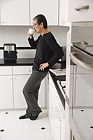 Man in kitchen, leaning on counter, drinking coffee, side profile to camera. - Asia Images Group