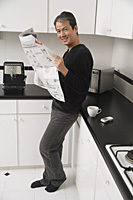 Man in kitchen, leaning on counter, holding newspaper and looking at camera smiling. - Asia Images Group