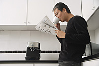 Man in kitchen, drinking coffee and reading paper - Asia Images Group