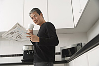 Man in kitchen, holding coffee cup and newspaper and looking at camera - Asia Images Group