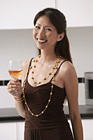 Woman in kitchen holding glass of wine, smiling at camera - Asia Images Group