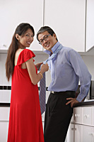 Man and woman in kitchen, getting ready for night out.  Woman tying mans tie, both looking at camera, smiling. - Asia Images Group