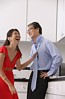 Man and woman in kitchen, woman laughing and tying mans tie.  Man with hands on hip. - Asia Images Group