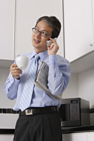 Business Man in kitchen, talking on phone, holding coffee cup and newspaper, multi tasking. - Asia Images Group