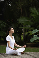 Woman in tropical setting, meditating on porch, eyes closed, in yoga OM posture, side view. - Asia Images Group