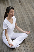 Woman meditating on porch, eyes closed, in yoga OM posture. - Asia Images Group