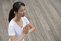 Woman on porch in yoga posture, hands in namaste, - Asia Images Group