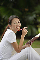 woman sitting outside in tropical setting, writing in journal, diary.  looking at camera, smiling. - Asia Images Group