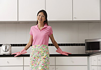 woman standing in kitchen, wearing gloves and apron for cleaning, looking at camera and smiling - Asia Images Group