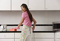 woman standing in kitchen, wearing gloves and apron and cleaning counter with big pink sponge, looking over shoulder at camera, smiling. - Asia Images Group