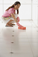 Woman cleaning floor with big pink sponge - Asia Images Group