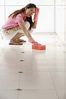 Woman tired of cleaning kitchen floor with big pink sponge - Asia Images Group