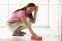 Woman cleaning kitchen floor with big pink sponge, tired - Asia Images Group