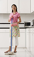 Woman with mop in kitchen, cleaning, looking at camera, smiling - Asia Images Group