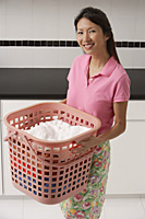 Woman doing laundry, holding laundry basket, smiling looking at camera - Asia Images Group