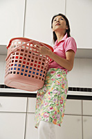 Woman doing laundry, holding laundry basket and wearing apron - Asia Images Group