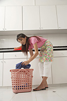 Woman doing laundry, taking laundry out of basket, leaning down - Asia Images Group