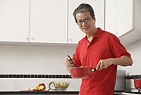 Man in kitchen cooking with sauce pan, looking at camera - Asia Images Group