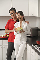 Man and woman in kitchen holding salad bowl and looking at camera smiling - Asia Images Group