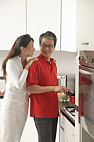 Man and woman in kitchen cooking - Asia Images Group