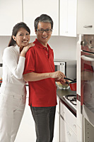 Man and woman in kitchen cooking, looking at camera, smiling - Asia Images Group