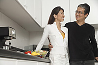 Man and woman in kitchen getting ready for a meal, smiling at each other. - Asia Images Group