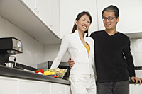 Man and woman in kitchen preparing a meal, smiling at camera - Asia Images Group