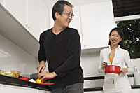 Man and woman in kitchen preparing a meal, cooking, smiling at each other - Asia Images Group