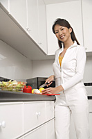 woman standing in kitchen cutting vegetables and fruit, cooking, smiling at camera - Asia Images Group