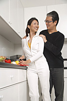 Man and woman standing in kitchen, cutting vegetables and smiling at each other - Asia Images Group