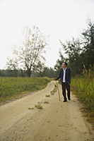 Man walking down dirt road, hiking - Asia Images Group