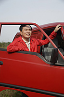 Man looking through window of open car door, outdoors, nature - Asia Images Group