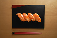 Four pieces of Salmon Sushi, nigiri on rice ball, chopsticks - Asia Images Group