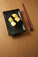 Two pieces of sushi, Tam ago Nigeria, sweet Japanese egg omelettes on sushi rice ball, chopsticks - Asia Images Group