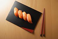 four pieces of salmon sushi, nigiri on rice ball, chopsticks - Asia Images Group