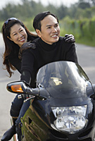Man and woman on motorcycle - Asia Images Group