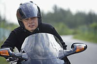 Man wearing helmet and riding motorcycle - Asia Images Group