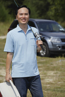 Man holding fishing pole over shoulder and cooler, car in background - Asia Images Group