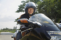 Mature woman riding motorcycle and wearing helmet - Asia Images Group