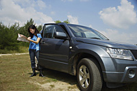 Woman standing next to SUV, looking at map - Asia Images Group