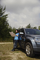 Woman leaning against SUV, reading map - Asia Images Group